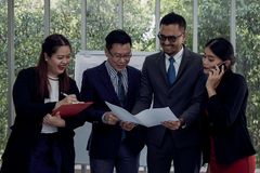 Four businessman and woman standing and check drawing together in meeting room stock images