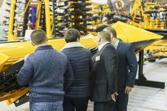 Four businessmen choose agricultural machinery stock photos