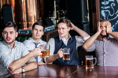 Four businessmen fans drinking beer and rejoice and shout togeth Stock Image