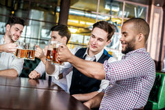 Four businessmen friends drink beer and spend time together in a Stock Photography