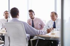 Four Businessmen Having Meeting Around Boardroom Table Stock Image