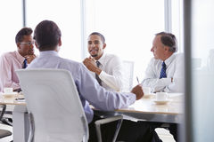 Four Businessmen Having Meeting Around Boardroom Table Stock Image