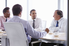 Four Businessmen Having Meeting Around Boardroom Table Royalty Free Stock Photos