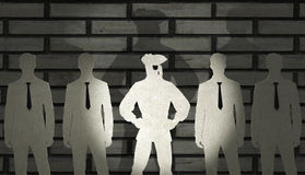 Four Businessmen and a Pirate. Four businessmen made of cardboard stand in front of a brick wall, casting large shadows Stock Images