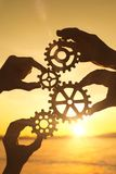 Four businessmen`s hands collect a puzzle of gears against the sunset. Business concept idea, strategy cooperation teamwork, creative stock images