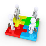 Four businessmen are united by puzzle pieces. Four 3d businessmen are standing on different colored puzzle pieces Royalty Free Stock Images