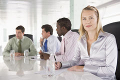Four businesspeople in a boardroom. With woman looking at camera stock photos