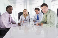 Four businesspeople in a boardroom Stock Images