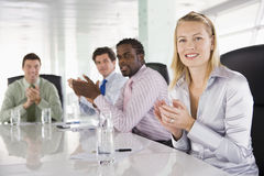 Four businesspeople in a boardroom applauding. Looking at camera royalty free stock photography