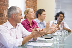 Four businesspeople in boardroom applauding.  royalty free stock photos