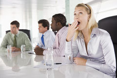 Four businesspeople in boardroom with one yawning Royalty Free Stock Photos