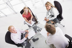 Four businesspeople in boardroom with paperwork. And smiling at camera stock photo