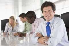 Four businesspeople in a boardroom smiling Stock Image