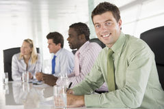 Four businesspeople in a boardroom smiling. Four businesspeople in a boardroom with one man looking at camera smiling stock photography
