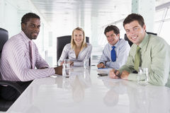 Four businesspeople in a boardroom smiling. Four businesspeople in a boardroom looking at camera smiling royalty free stock photos