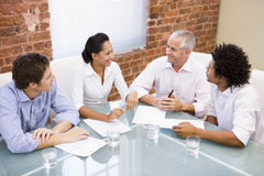 Four businesspeople in boardroom smiling Stock Image