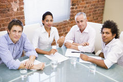 Four businesspeople in boardroom smiling. Looking at camera stock photography