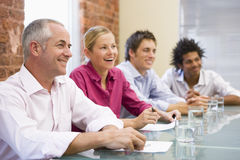 Four businesspeople in boardroom smiling.  stock photo