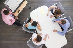 Four businesspeople at boardroom table Royalty Free Stock Photos