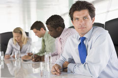 Four businesspeople in a boardroom writing Royalty Free Stock Image