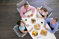 Four businesspeople eating at boardroom table Royalty Free Stock Images