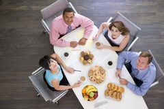 Four businesspeople eating at boardroom table Stock Photos
