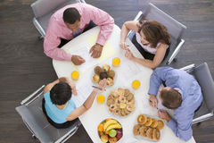 Four businesspeople eating at boardroom table. Four businesspeople eating breakfast at boardroom table stock images