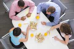 Four businesspeople eating at boardroom table stock photography