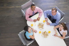 Four businesspeople eating at boardroom table stock image