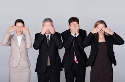 Four businesspeople holding their eyes shut Stock Images