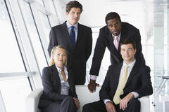 Four businesspeople in office lobby. Four businesspeople sitting in office lobby smiling Royalty Free Stock Images