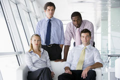 Four businesspeople in office lobby. Three businesspeople sitting in office lobby looking at camera royalty free stock photography