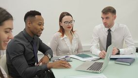 The four businesspeople prepares for the presentation siting at the big table in bright office. The two businesswoman wears white blouse, one businessman in stock footage
