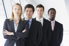 Four businesspeople standing in corridor stock photo