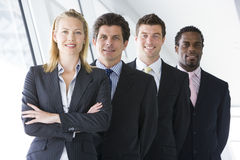 Four businesspeople standing in corridor smiling Stock Photo