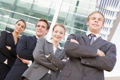 Four businesspeople standing outdoors smiling Royalty Free Stock Photo