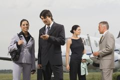 Four businesswomen and businessmen at an airport Royalty Free Stock Image