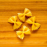 Four butterflies  for italian pasta on wood background. Dietary food. Stock Images