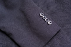 Four buttons on a black business jacket sleeve Stock Images