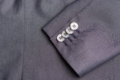 Four buttons on a grey business jacket sleeve Stock Images
