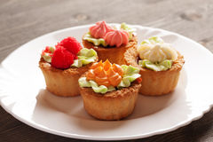 Four cake basket on a white plate Royalty Free Stock Photo
