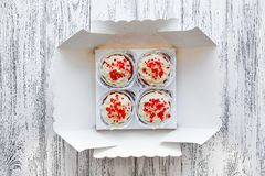 Four cake cakes in a box on white old vintage boards background stock photos