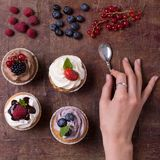 Sweet berries cakes with woman hand with fresh berries on wooden table top view royalty free stock image