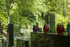 Four candle lanterns on tomb stones in graveyard in summer stock images