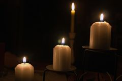 Four candles. Candles glowing in the dark royalty free stock photography