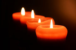 Four candles. In the darkness Stock Photos