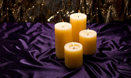 Four candles over purple velvet Stock Image