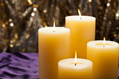 Four candles over purple velvet Royalty Free Stock Image