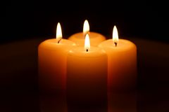 Four candles with reflection. Group of four candles burning on the dark background, with reflection Stock Photography