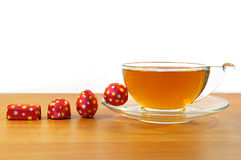 Four candys and a cup of tea Royalty Free Stock Photo